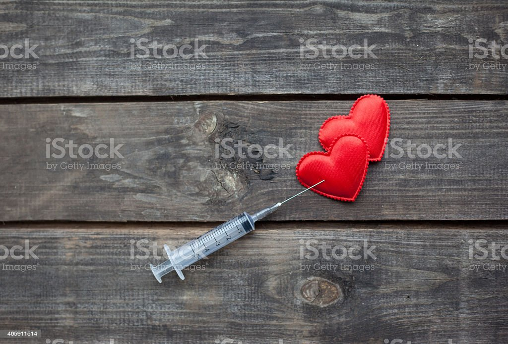 red hearts and syringe on wooden background. Drug Addiction Concept stock photo