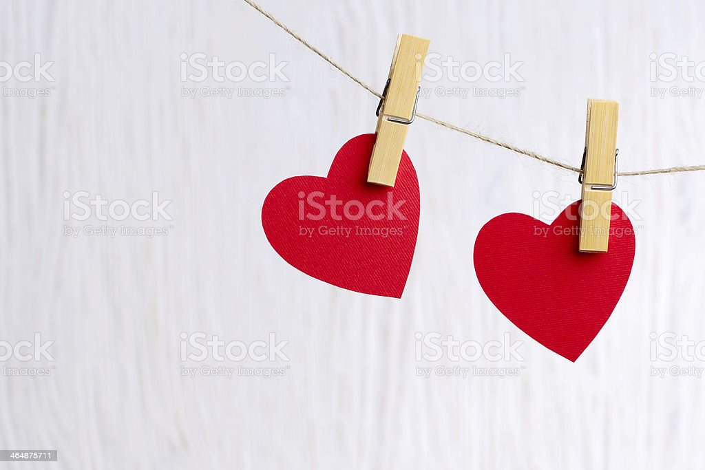 red hearts hanging on wooden background stock photo