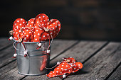 Red hearts in zinc bucket on wooden background in vintage