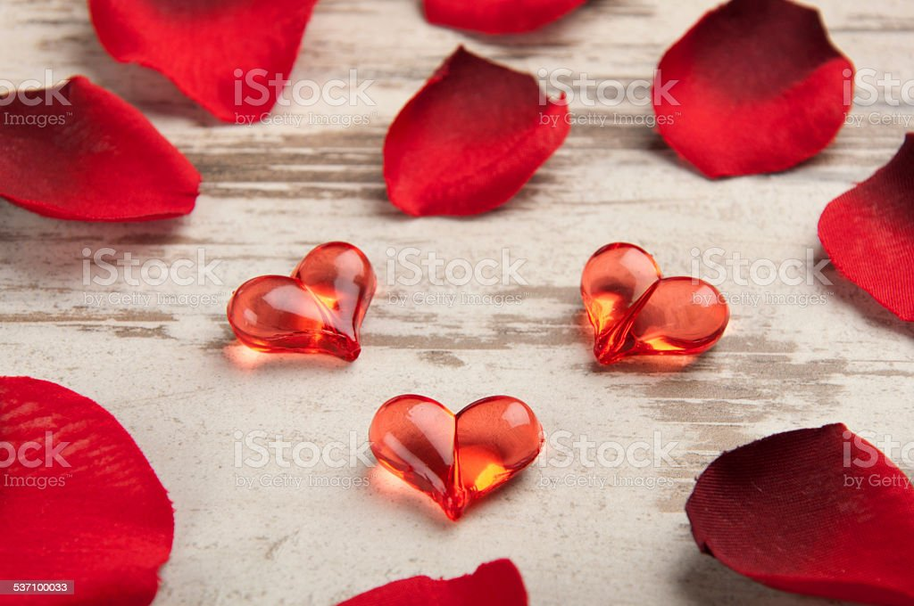 red hearts on the wooden board with petals stock photo