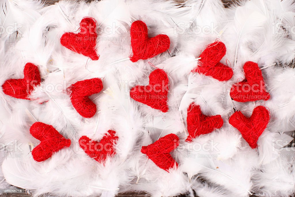 red hearts on white feathers stock photo