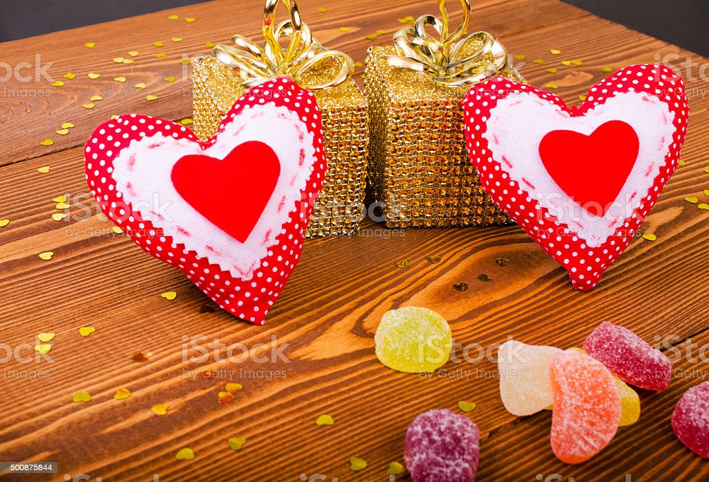 Red hearts, two golden gift and fruit candy on wooden background.