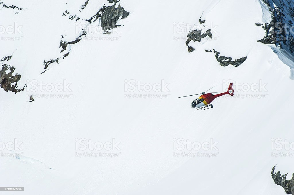 Red Helichopter flying above snow mountain in Jungfrau Region royalty-free stock photo