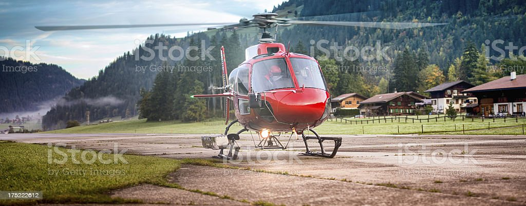 Red Helicopter about to take off in Switzerland Alps stock photo