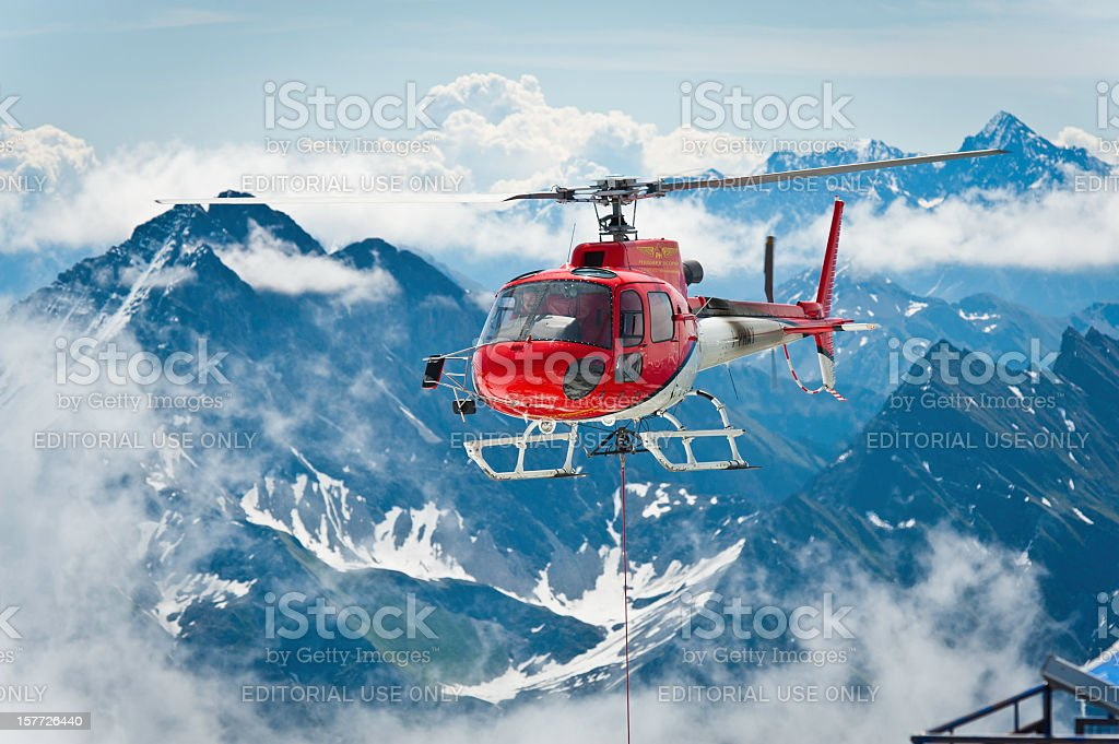 Red helicopter flying dramatic mountain scenery Alps stock photo