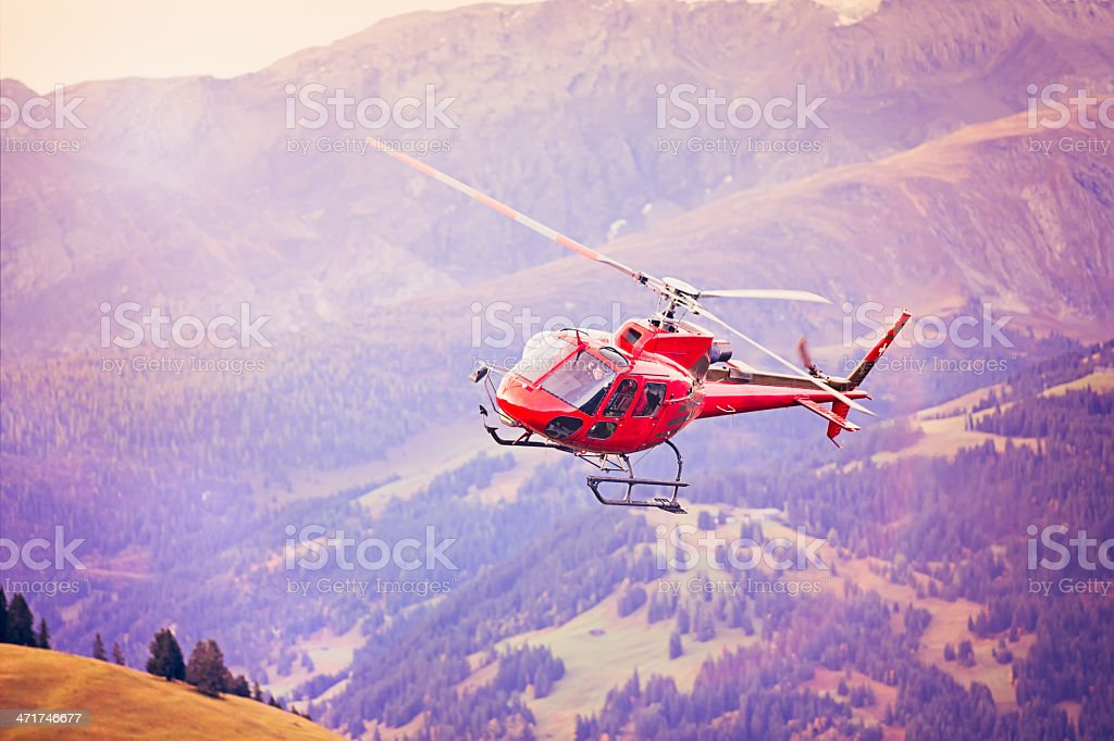 Red helicopter landing in Alpine Switzerland royalty-free stock photo