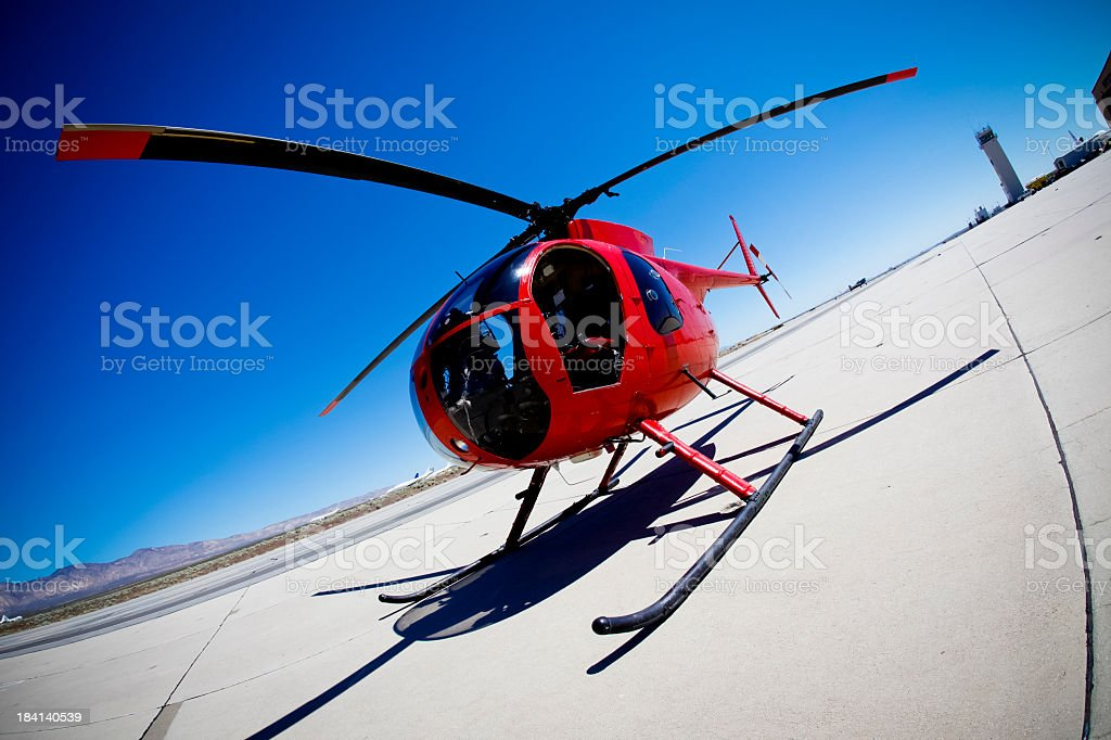 Red helicopter landing on sunny day stock photo