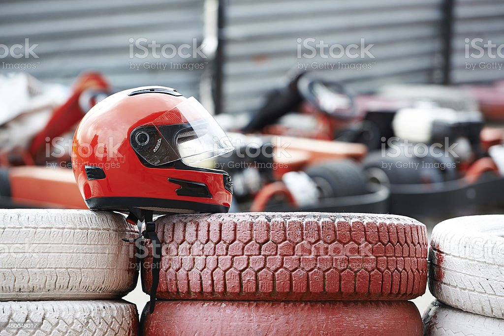 Red helmet with visor is on tires stock photo