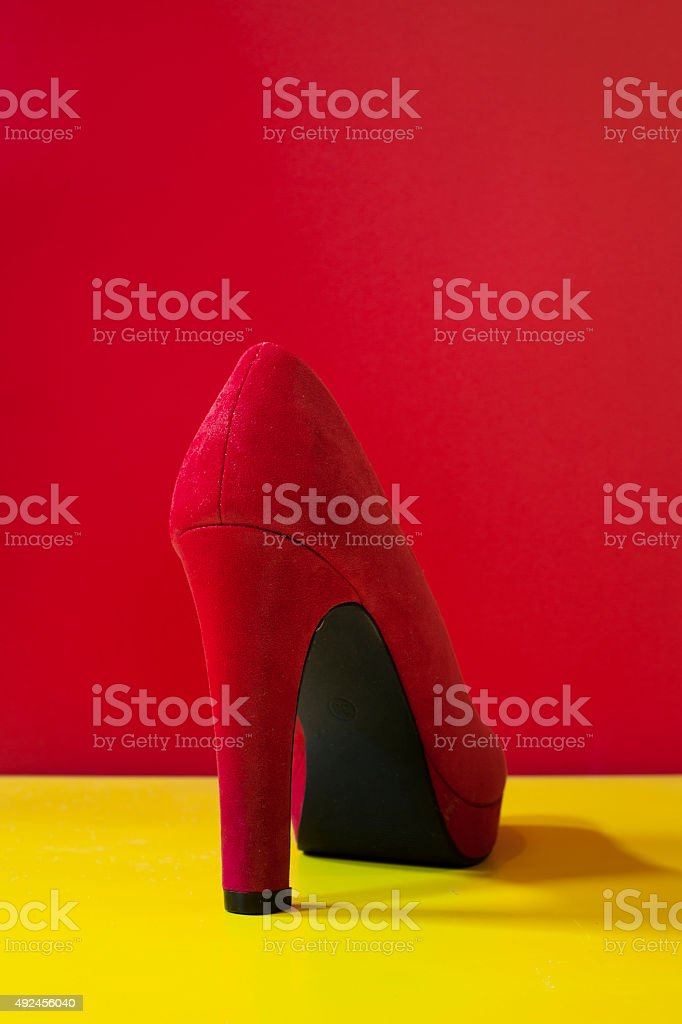 Red High Heel on yellow ground stock photo