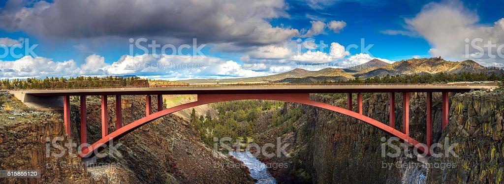 Red  highway  bridge across ravine in high desert panorama stock photo