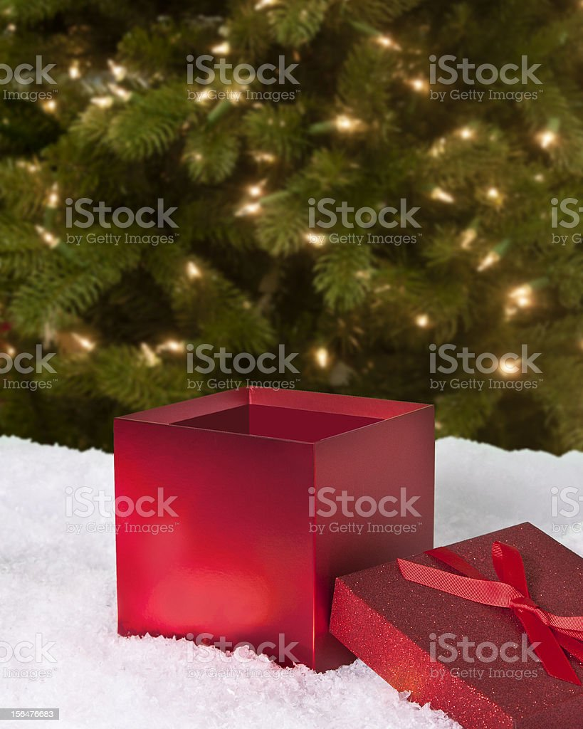 Red Holiday gift box, snow and lighted evergreen tree background stock photo