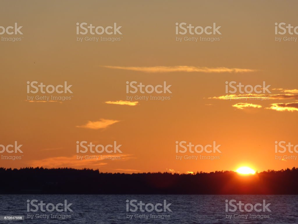 Red horizon with clouds and sunset over the Vättern in Sweden stock photo