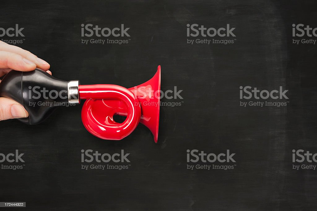 Red horn or trumpet against blank chalkboard stock photo