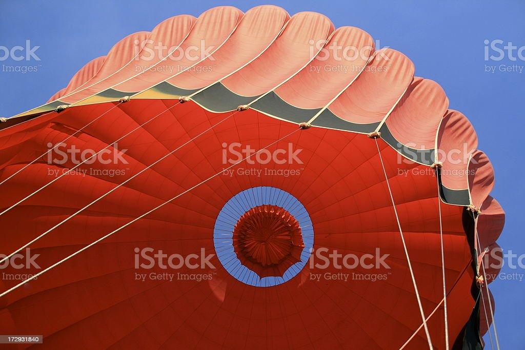 Red hot air balloon deflating stock photo