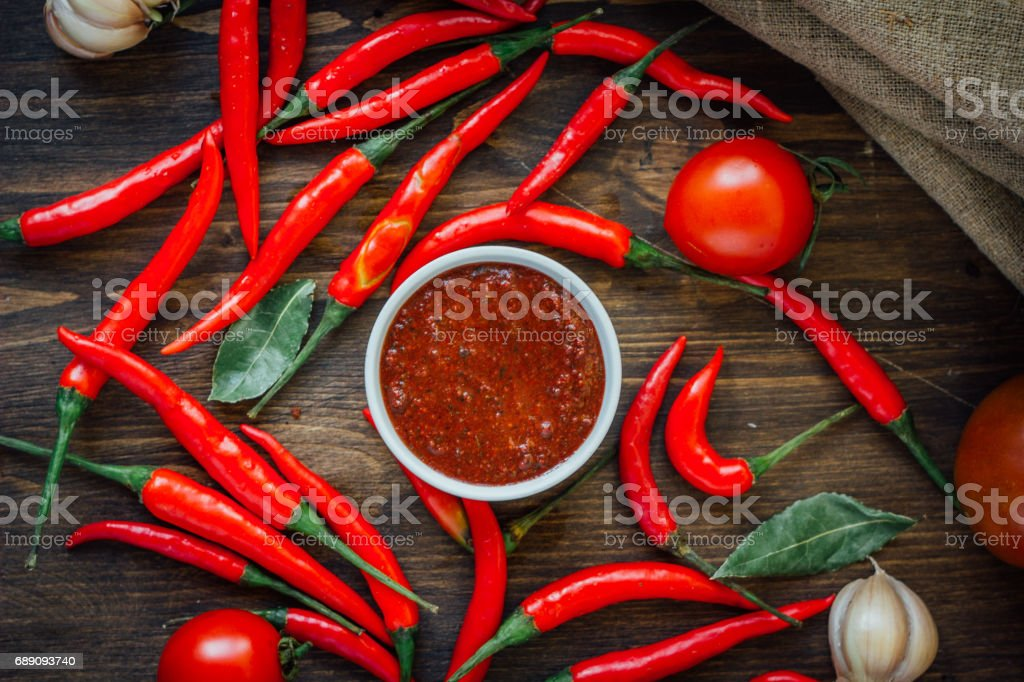Red hot chili peppers and salsa or adjika in white ceramic bowl. stock photo