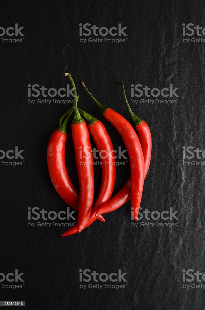 Red hot chili peppers on a dark, stone background stock photo