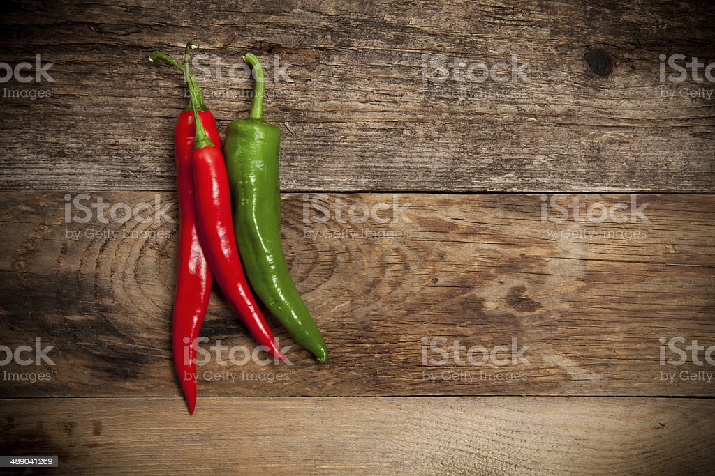 Red hot chili peppers on old wooden table stock photo