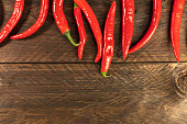 Red hot chili peppers on wooden texture with copyspace