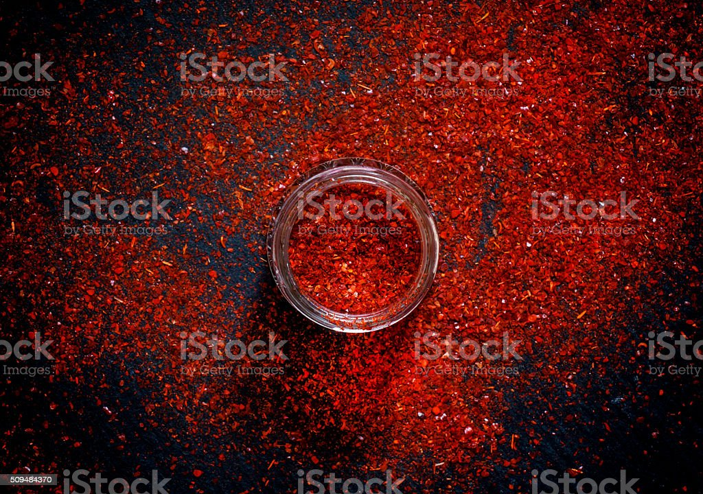 Red hot ground  chili pepper, scattered on a dark background stock photo