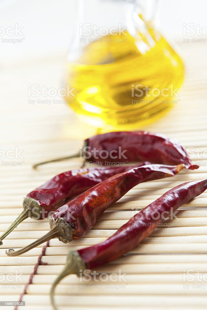Red hot peppers and bottle vegetable oil on bamboo mat royalty-free stock photo