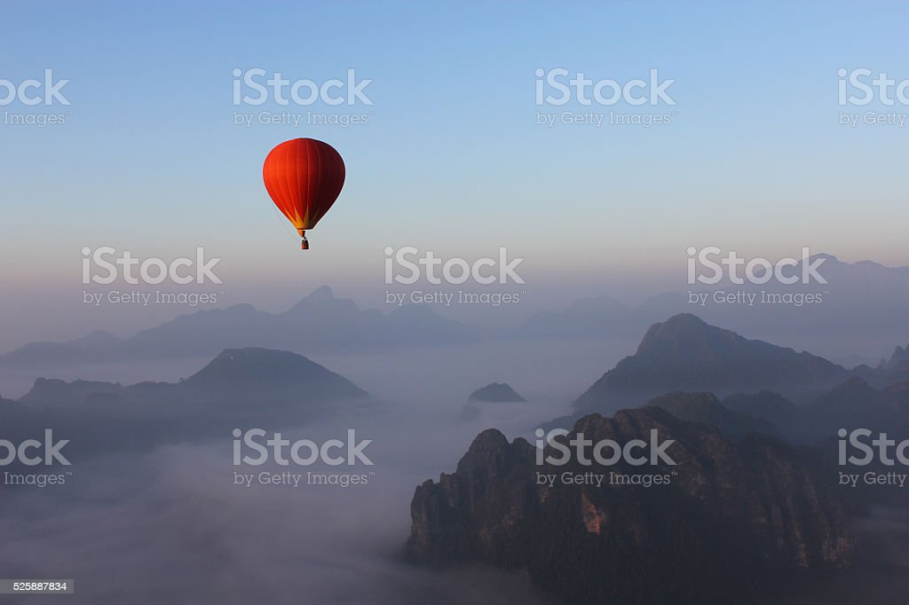 Red Hot-air Balloon float over Misty Mountain stock photo