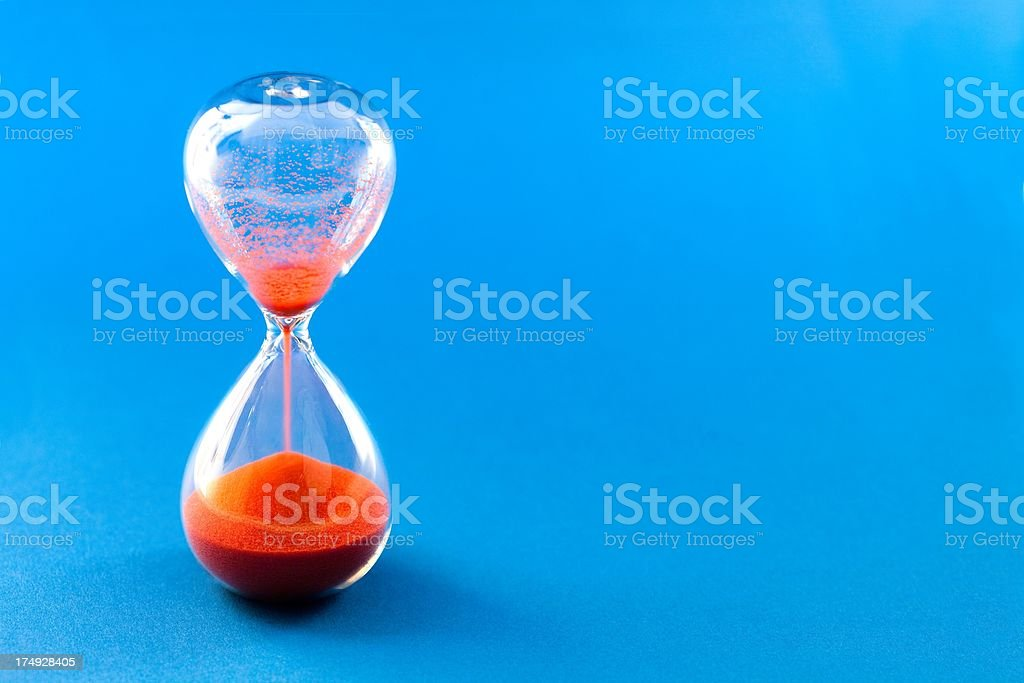Red hourglass on blue background stock photo