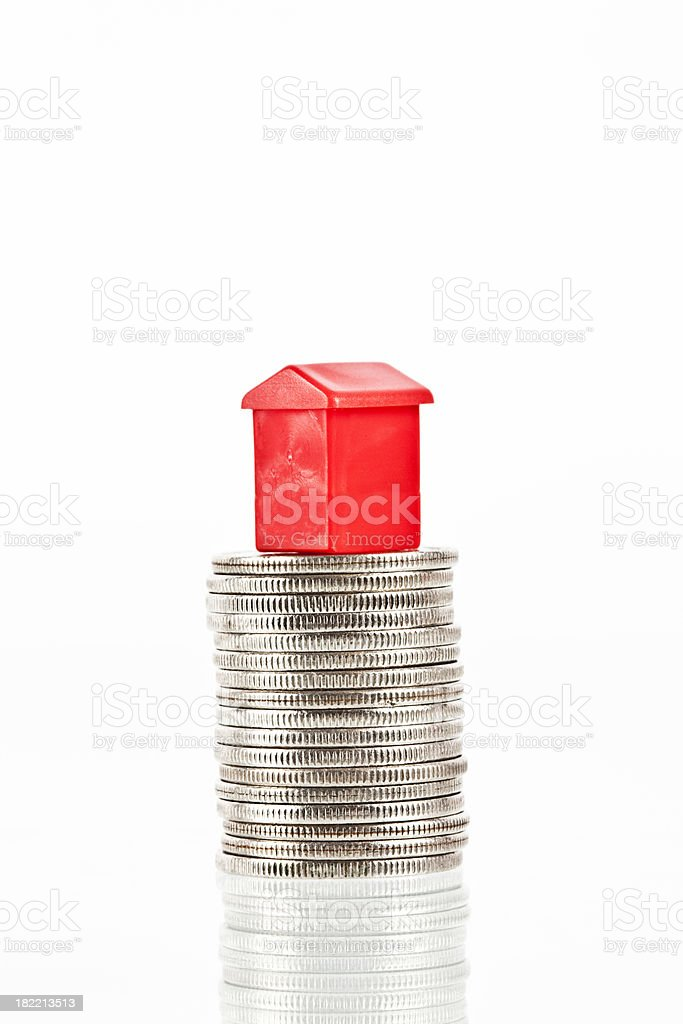 Red house on a stuck of coins. stock photo