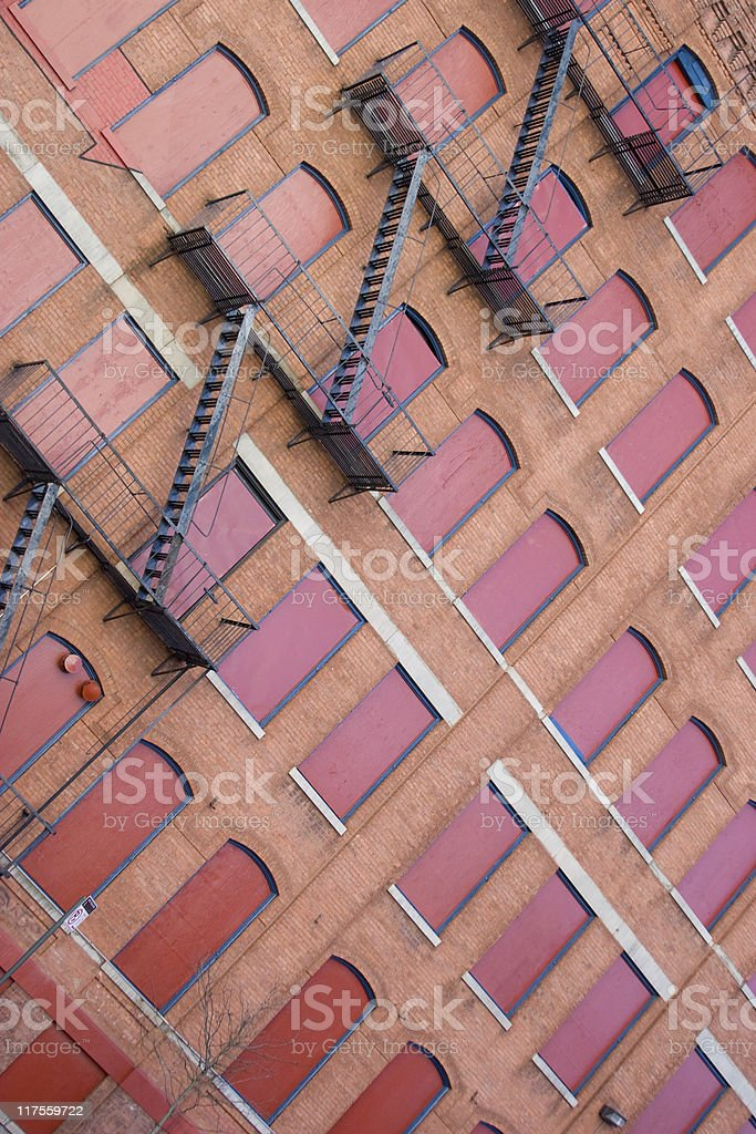 red house wall with boarded-up windows and fire escape ladder royalty-free stock photo
