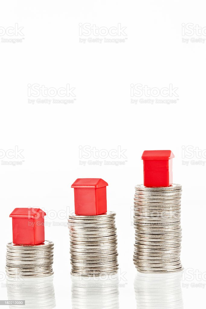 Red houses on a stuck of coins. stock photo