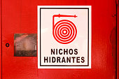 Red hydrant cabinet with sign saying 'Niche hydrant' in Spanish