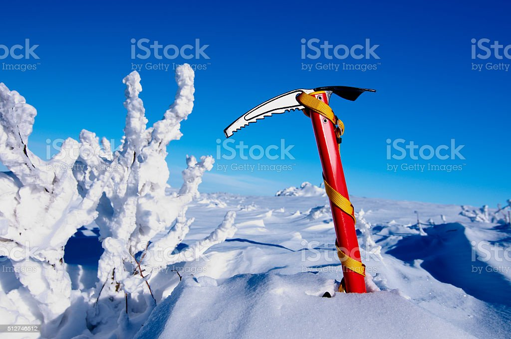 Red ice pickaxe in a white snow in the mountains stock photo