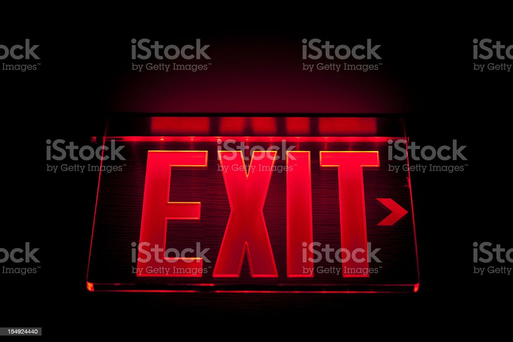 A red Illuminated exit sign on black stock photo