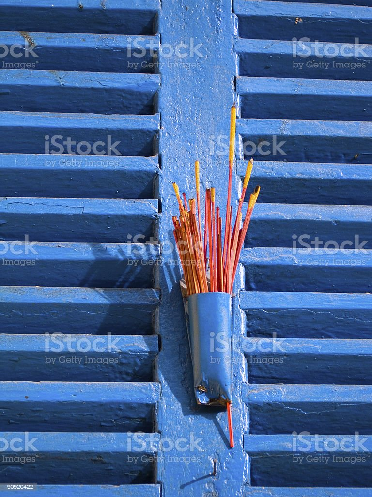 Red Incense on Blue Window Shutters royalty-free stock photo