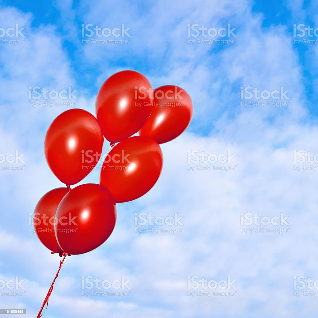 Red inflatable balloons on the sky background stock photo