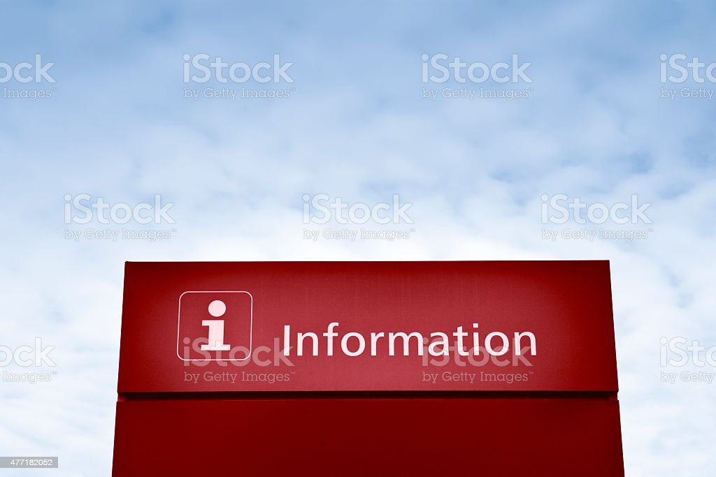 Red information sign against a blue sky stock photo