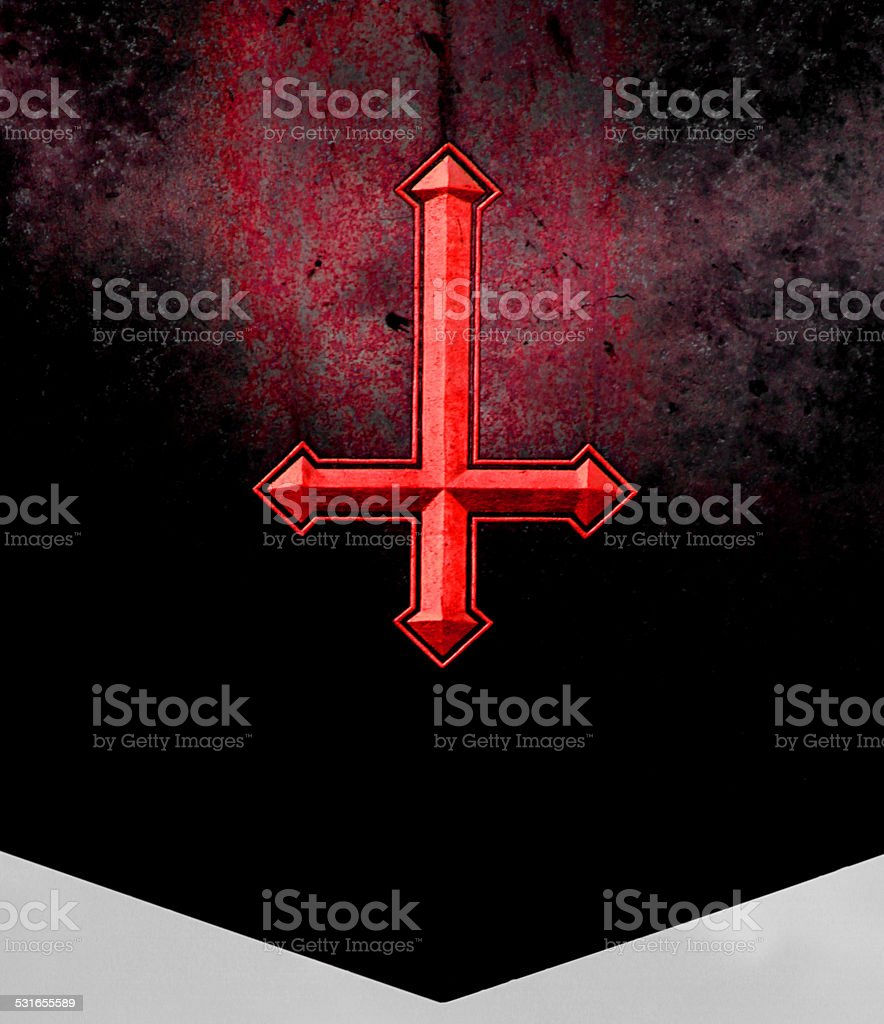 Red inverted cross engraved on a gravestone stock photo