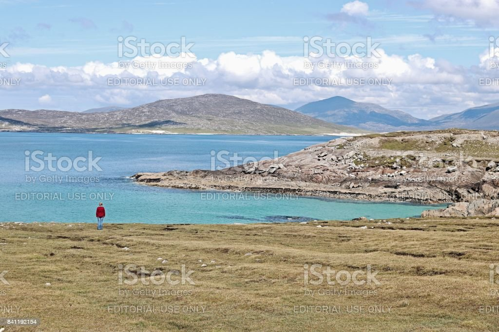 Red jacket Person dwarfed by beautiful Harris Landscape stock photo
