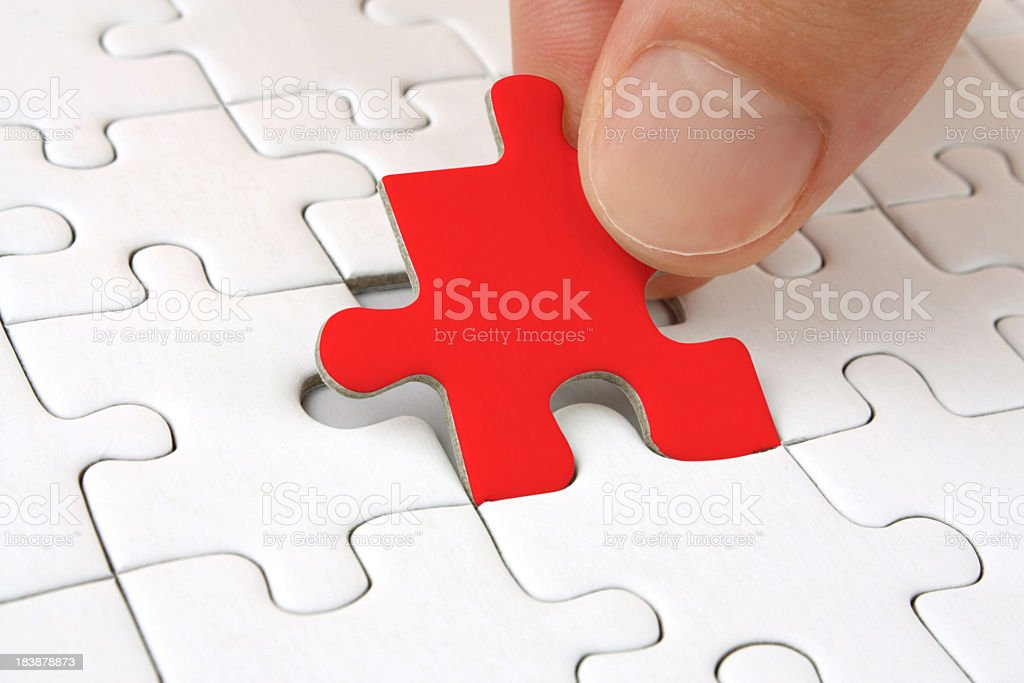 Red jigsaw puzzle piece being placed in all-white puzzle royalty-free stock photo