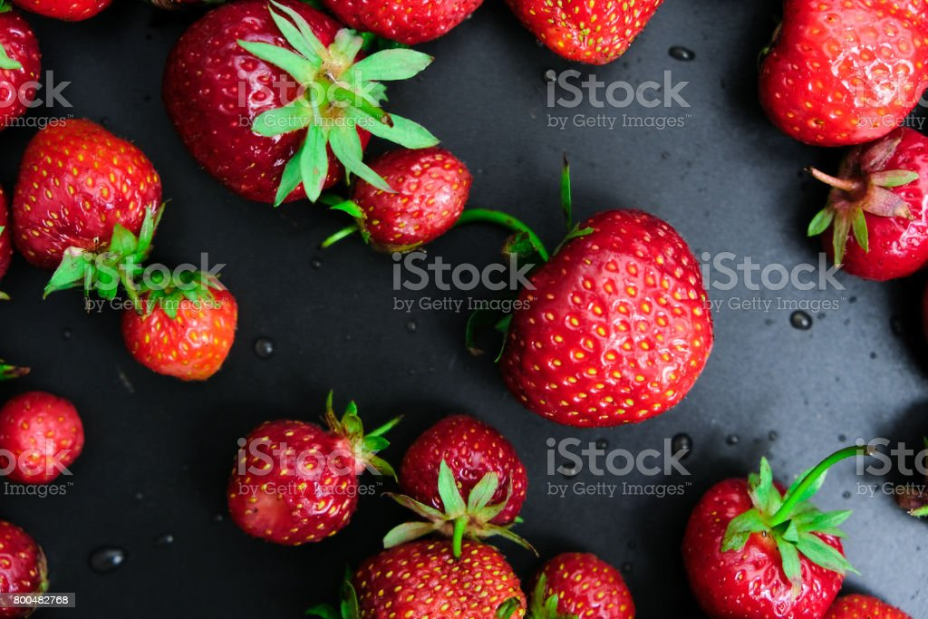 Red juicy strawberry on a dark black wooden background.The droplets of water. Juiciness, vitamins and healthy food. stock photo