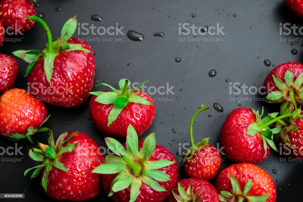 Red juicy strawberry on a dark black wooden background.The droplets of water. Juiciness, vitamins and healthy food. Place for print stock photo