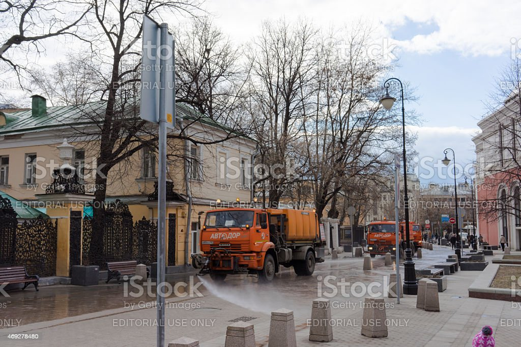 Red KAMAZwatering and cleaning machines at the city street. stock photo