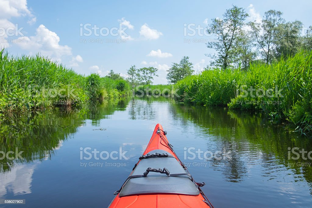 Red kayak in a canal in nature reserve in spring stock photo