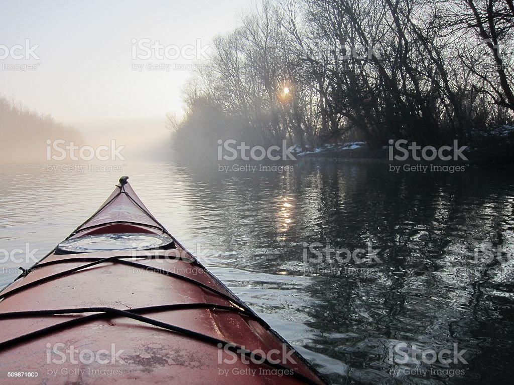 Red kayak in the foggy winter Danube river stock photo