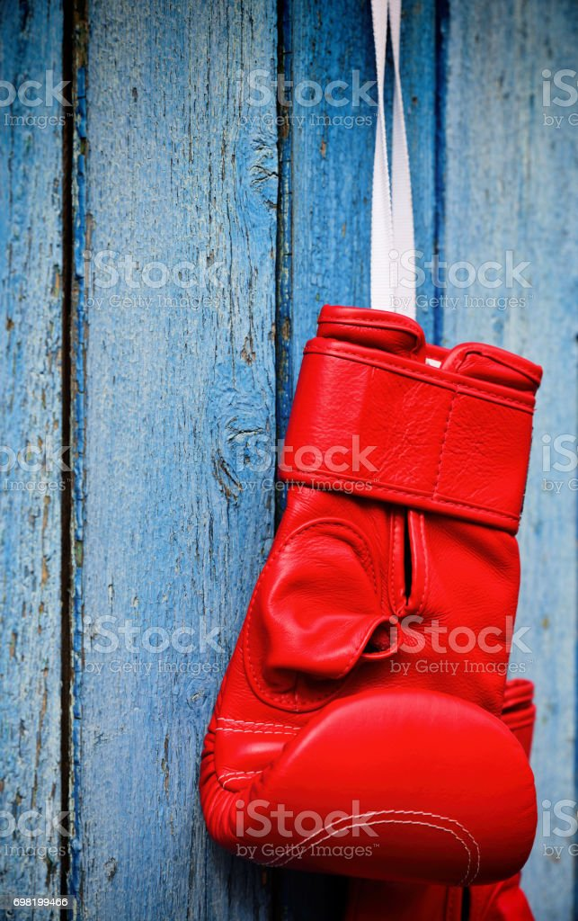 Red kickboxing glove hanging on a wooden blue surface stock photo
