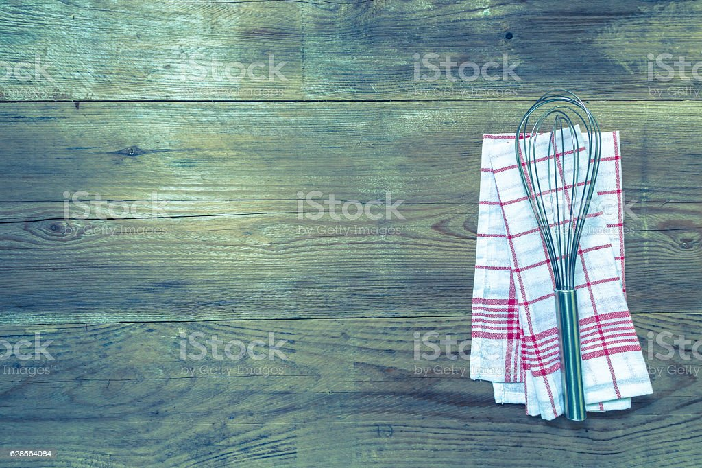 Red kitchen towel with whisk on a wood wood background stock photo