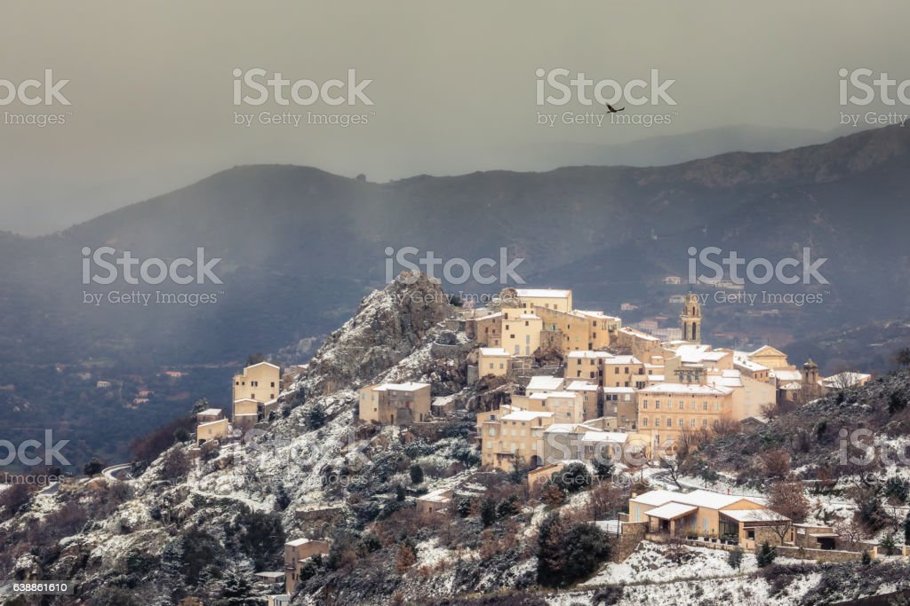 Red Kite soaring over mountain village of Speloncato in Corsica stock photo