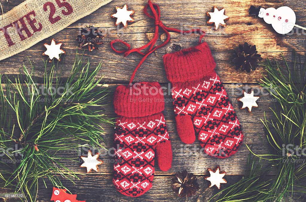 Red knitted mittens, pine tree twigs and gingerbread cookies stock photo