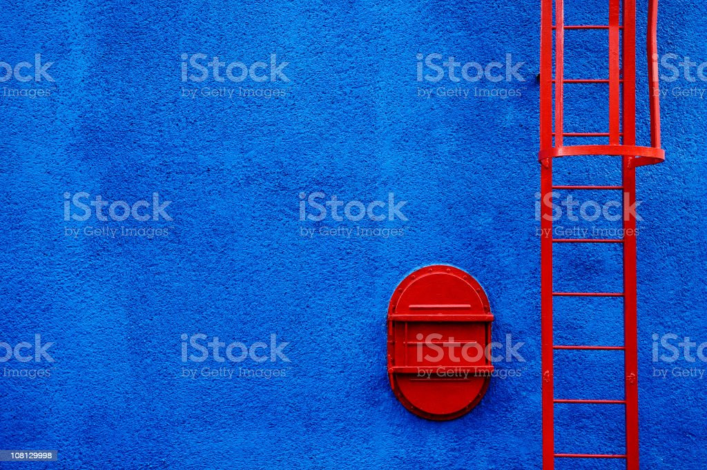 Red Ladder and Trap Door on Blue Wall stock photo