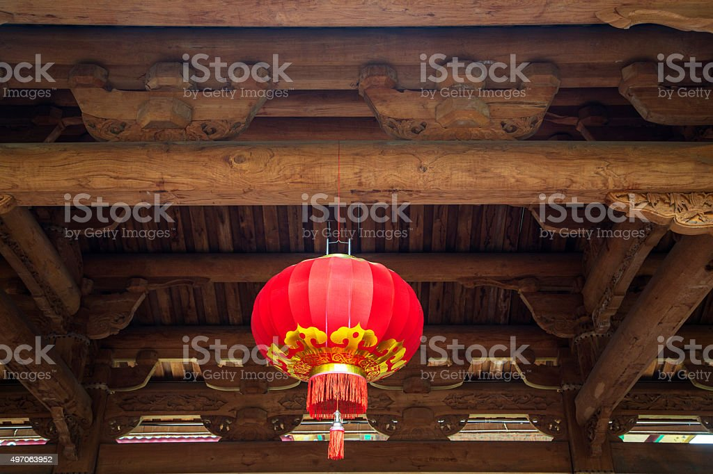 red lantern hanging from ancient wooden architecture stock photo