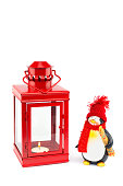 Red lantern with penguin figurine on white